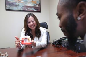 dentist Kelly Hong showing a patient a dental implant in Victorville, CA.